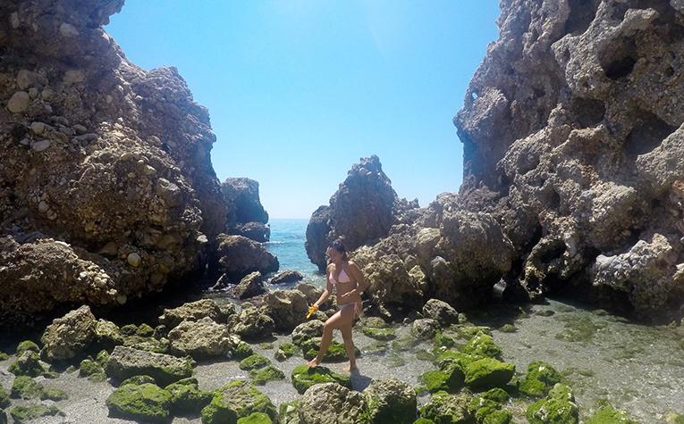 Barnacle hunting on a beach in Nerja, Spain