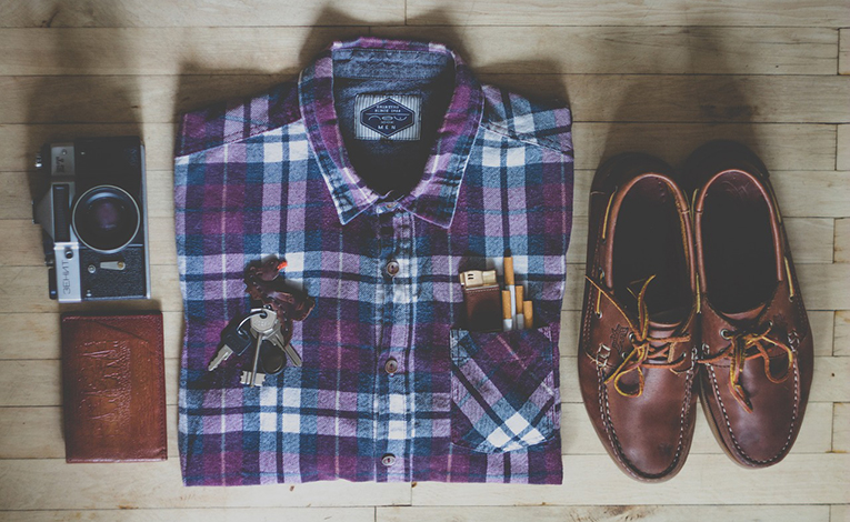 folded flannel shirt, leather shoes, a wallet, keys, and a camera