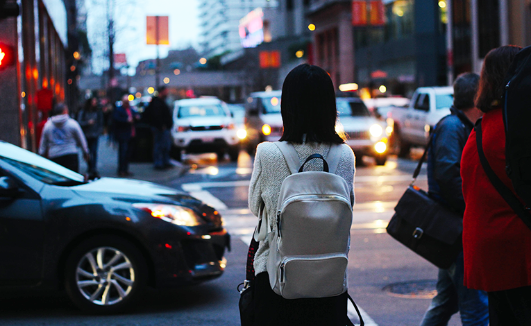 Girl walking across a busy street at night