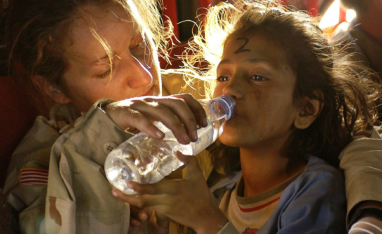 Humanitarian aid woman giving water to a refugee child