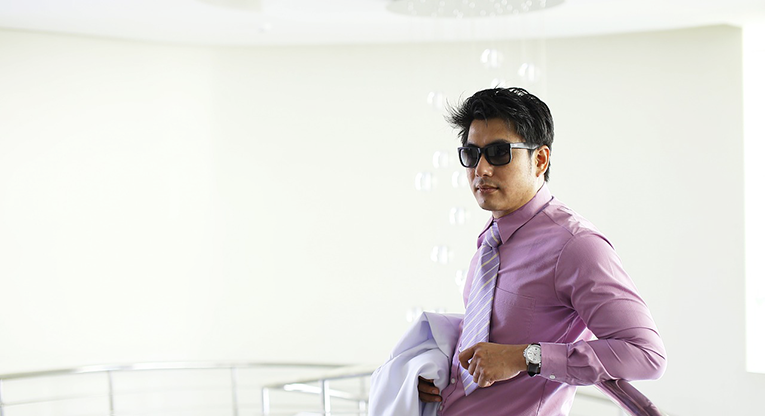 Man dressed in business attire wearing sunglasses