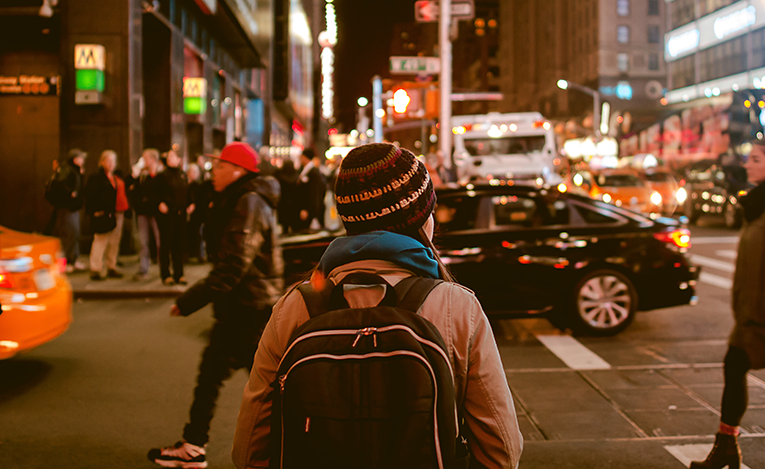 Girl wearing a backpack walking down a city street at night