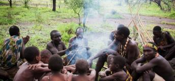 Hadza tribesmen sitting around a day-fire.
