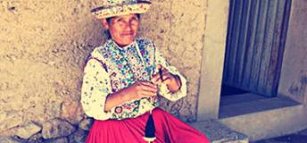 A woman living in a village in Canyon de Colca, Peru demonstrates local weaving skills for volunteers.