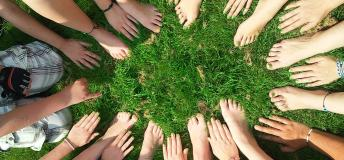 Circle of people with their hands in the grass