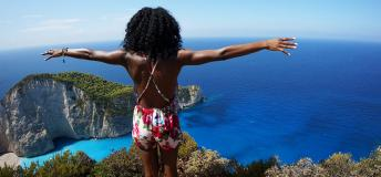 African American woman standing on a cliff overlooking the ocean