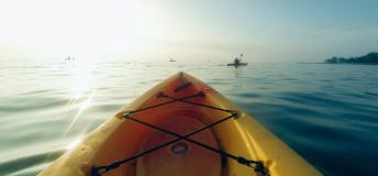 Edge of a kayak looking out over water