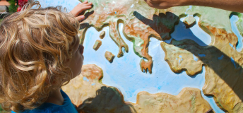 a little boy looking and pointing at a globe