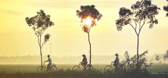 Three individuals riding a bicycle in a rural area of China.