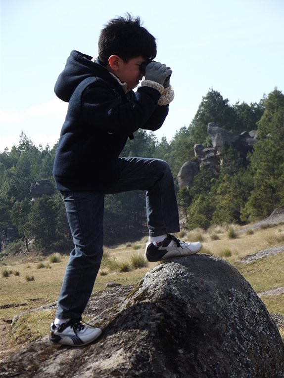 kid conquering new heights on top of a rock