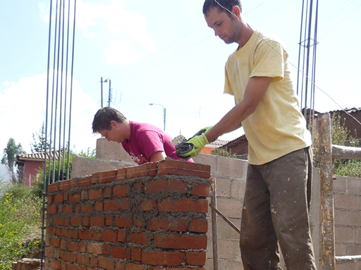 Construction volunteers laying bricks in Cusco, Peru