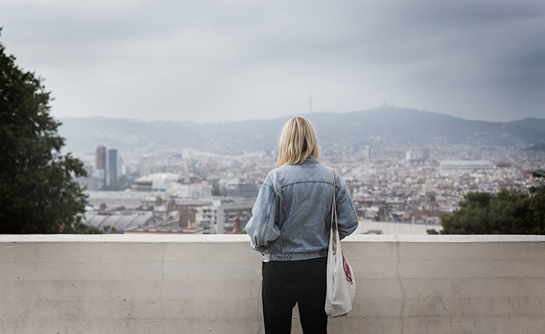 Girl looking at Barcelona from a balcony