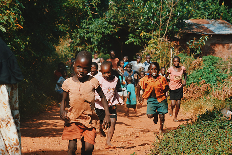 Children smiling and running along a dirt path