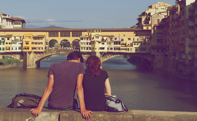 man and woman sitting on bridge looking out at river