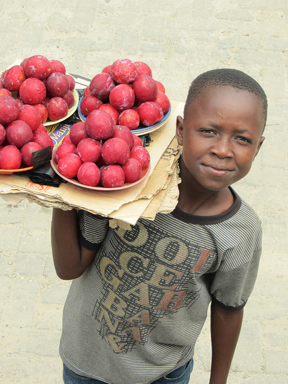 A child in Zambia selling fruits